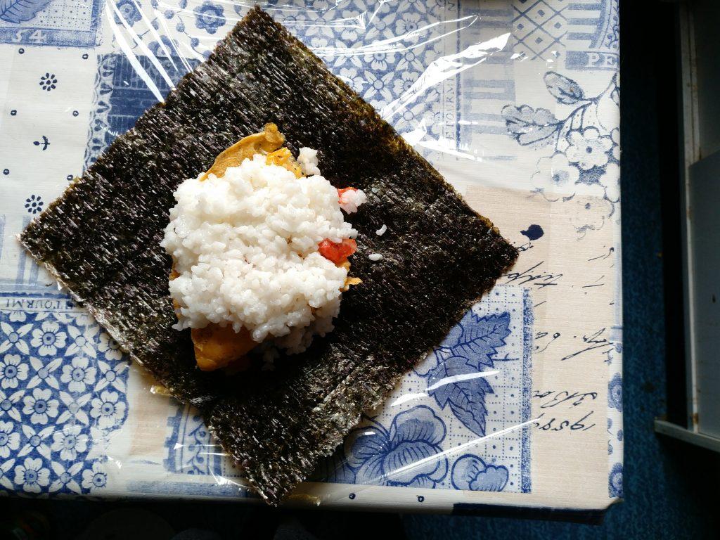 Noriblatt mit beiden Reisschichten und dem Omelett dazwischen